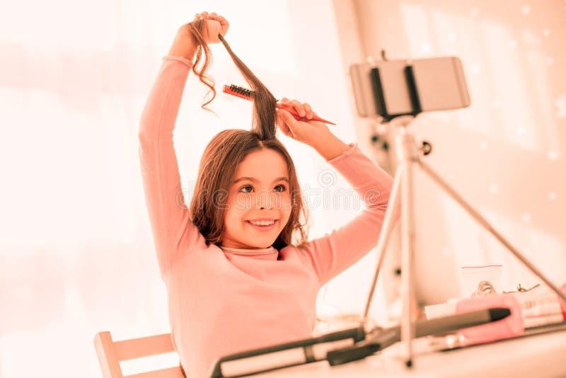 Χαριτωμένο εύθυμο θετικό κορίτσι που χρησιμοποιεί μια βούρτσα γηα τα μαλλιά στοκ φωτογραφία με δικαίωμα ελεύθερης χρήσης