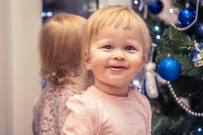Χαριτωμένο εύθυμο κοριτσάκι που περιμένει το δώρο Χριστουγέννων με το χριστουγεννιάτικο δέντρο στο υπόβαθρο στο σπίτι στοκ φωτογραφίες με δικαίωμα ελεύθερης χρήσης