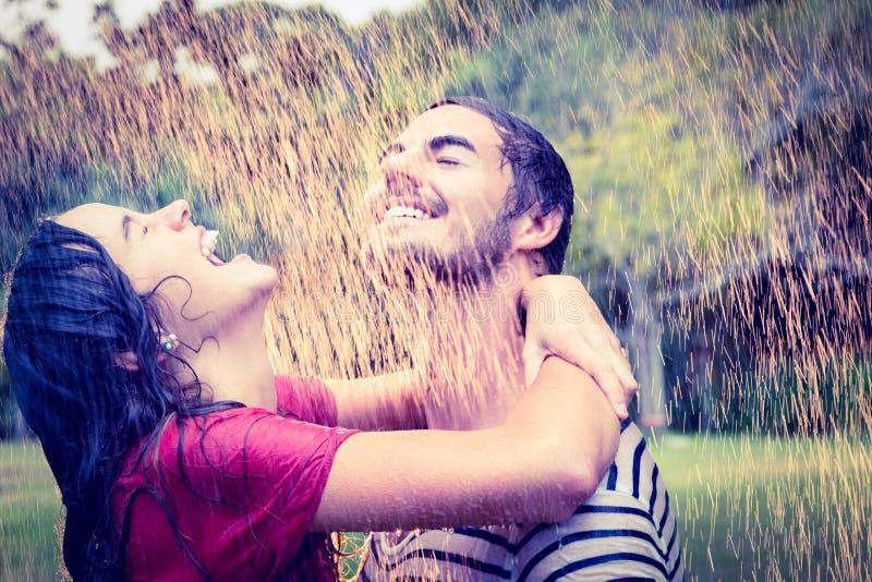 Χαριτωμένο ζεύγος που αγκαλιάζει κάτω από τη βροχή στοκ εικόνα