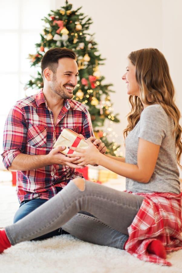 Χαριτωμένο ζεύγος που ανταλλάσσει τα χριστουγεννιάτικα δώρα στο πρωί Χριστουγέννων στοκ φωτογραφία