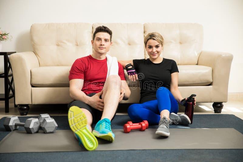 Χαριτωμένο ζεύγος που παίρνει ένα σπάσιμο από την άσκηση στοκ φωτογραφίες