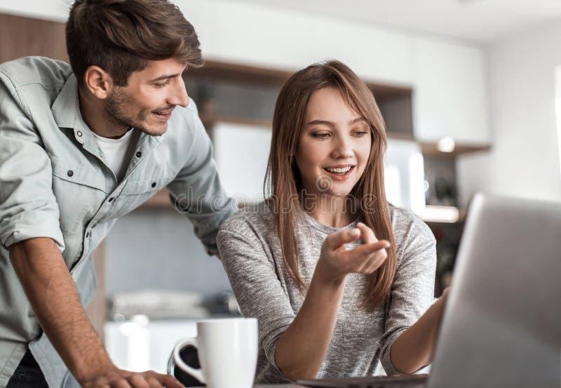 Χαριτωμένο ζεύγος που χρησιμοποιεί το lap-top μαζί στο σπίτι στην κουζίνα στοκ εικόνες με δικαίωμα ελεύθερης χρήσης