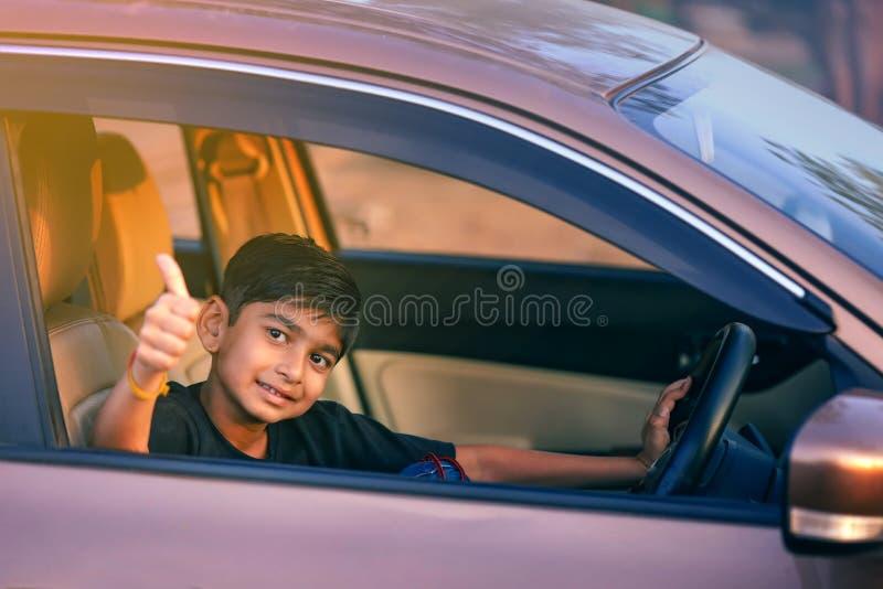Χαριτωμένο ινδικό παιδί που παρουσιάζει πλήγματα από το παράθυρο αυτοκινήτων στοκ φωτογραφίες με δικαίωμα ελεύθερης χρήσης