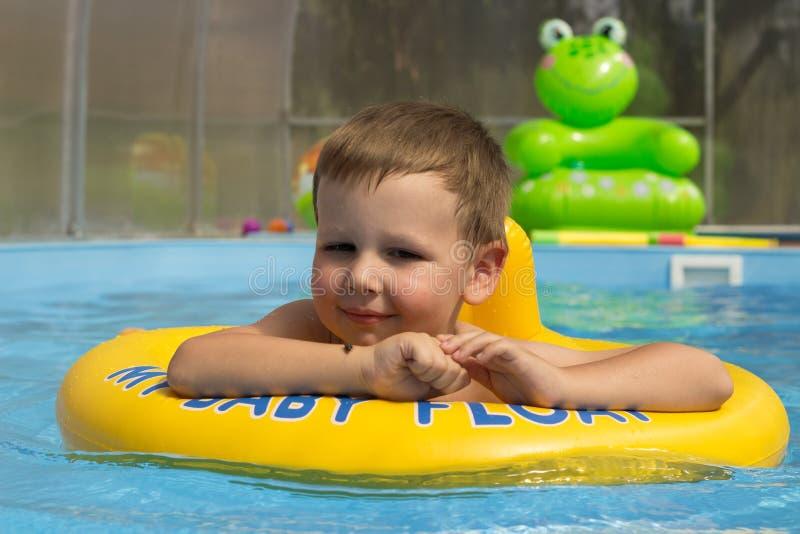 Χαριτωμένο και αστείο μικρό κορίτσι στην πισίνα, που κολυμπά στο διογκώσιμο δαχτυλίδι, έννοια τρόπου ζωής Ο διογκώσιμος κύκλος Κα στοκ φωτογραφία