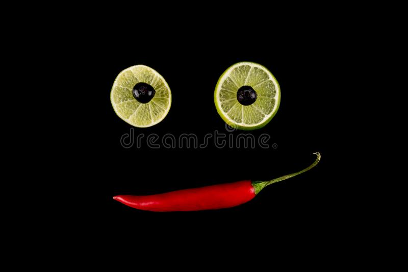 Χαριτωμένο και αστείο πρόσωπο smiley φιαγμένο από κόκκινο πιπέρι, ασβέστη και βακκίνια τσίλι Δημιουργικό concep τέχνης τροφίμων στοκ φωτογραφία