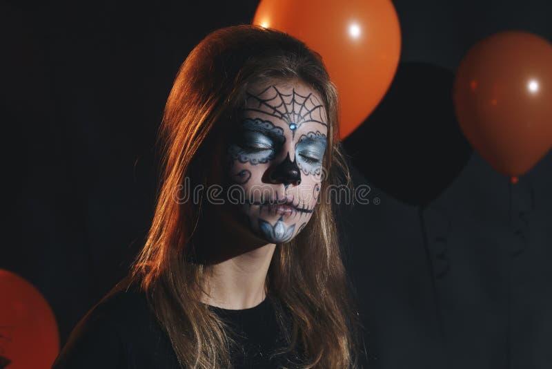 Χαριτωμένο και όμορφο κορίτσι με τις μακριές μπούκλες που θέτουν για αποκριές που φορούν ένα τεράστιο μαύρο και πορτοκαλί καπέλο στοκ φωτογραφία με δικαίωμα ελεύθερης χρήσης