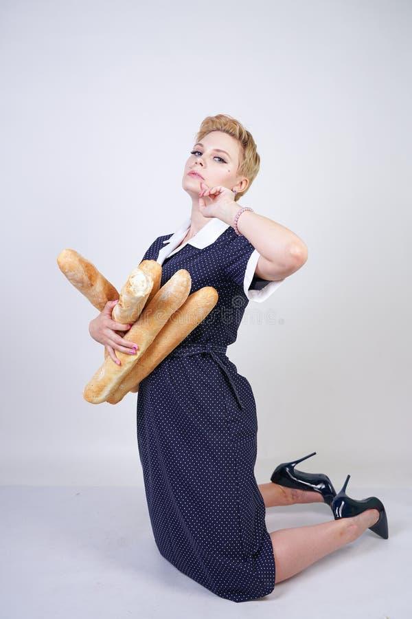 Χαριτωμένο καυκάσιο κορίτσι pinup που φορά το εκλεκτής ποιότητας φόρεμα σημείων Πόλκα και που κρατά τα baguettes σε ένα άσπρο υπό στοκ εικόνα