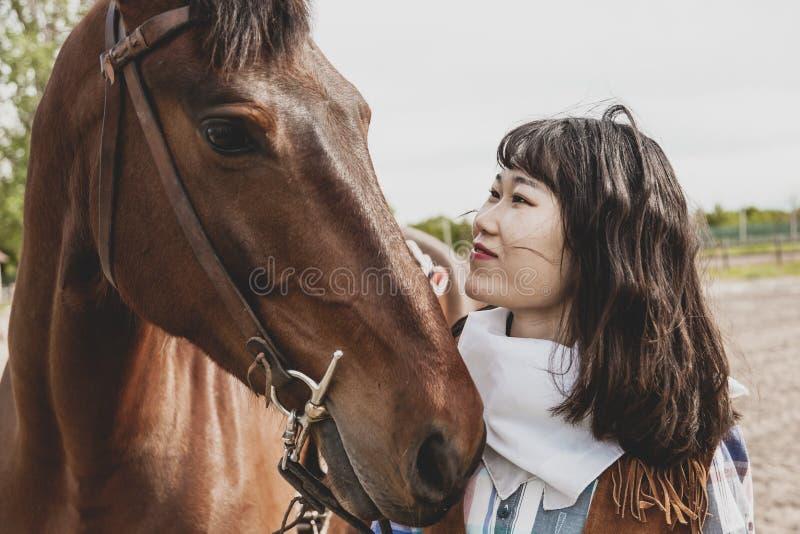 Χαριτωμένο κινεζικό cowgirl φροντίζοντας το άλογό της στοκ εικόνες