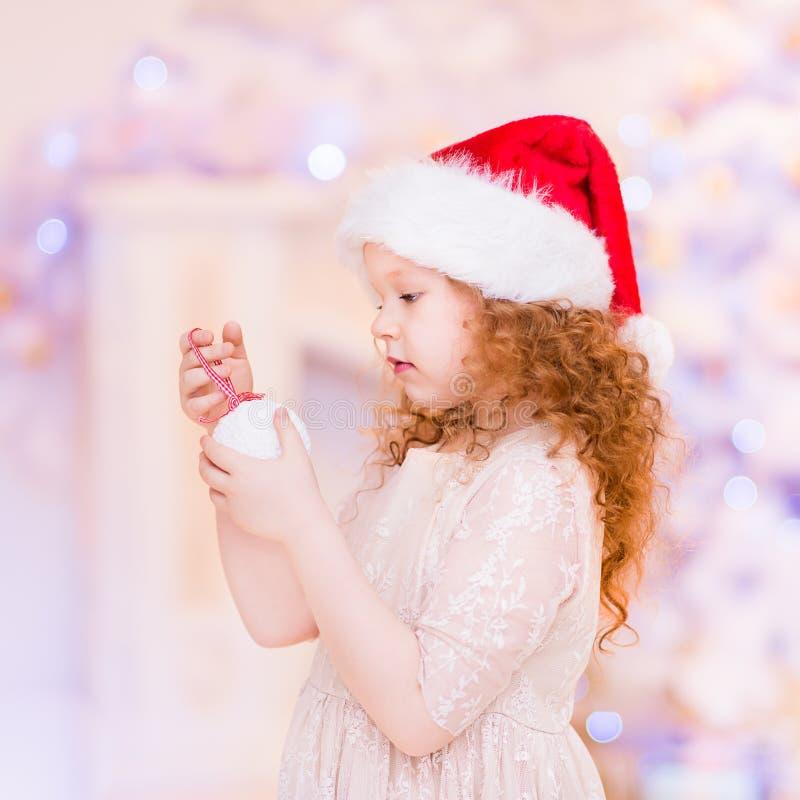 Χαριτωμένο κοκκινομάλλες μικρό κορίτσι που φορά το καπέλο Άγιου Βασίλη στοκ εικόνα με δικαίωμα ελεύθερης χρήσης