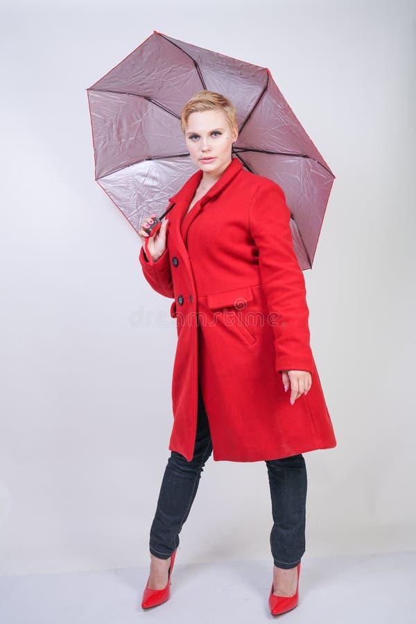 Χαριτωμένο κοντό chubby κορίτσι τρίχας σε ένα σύγχρονο παλτό μαλλιού πόλεων που κρατά μια κόκκινη ομπρέλα και που θέτει σε ένα άσ στοκ φωτογραφίες