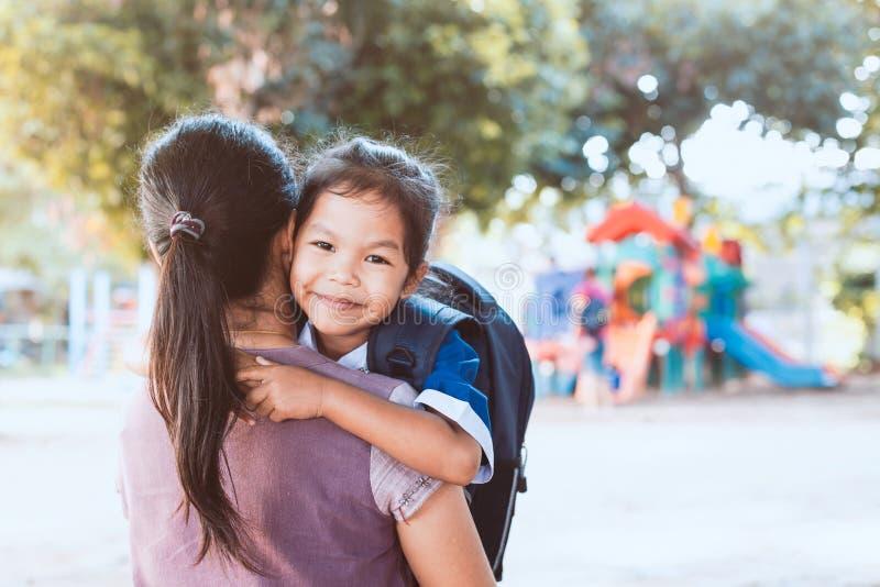 Χαριτωμένο κορίτσι ασιατικών μαθητών με το σακίδιο πλάτης που αγκαλιάζει τη μητέρα της στοκ φωτογραφία με δικαίωμα ελεύθερης χρήσης