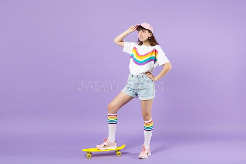 Χαριτωμένο κορίτσι εφήβων στα ζωηρά ενδύματα που στέκονται με κίτρινο skateboard, φυσώντας γόμμα φυσαλίδων, που φαίνεται κατά μέρ στοκ φωτογραφία με δικαίωμα ελεύθερης χρήσης