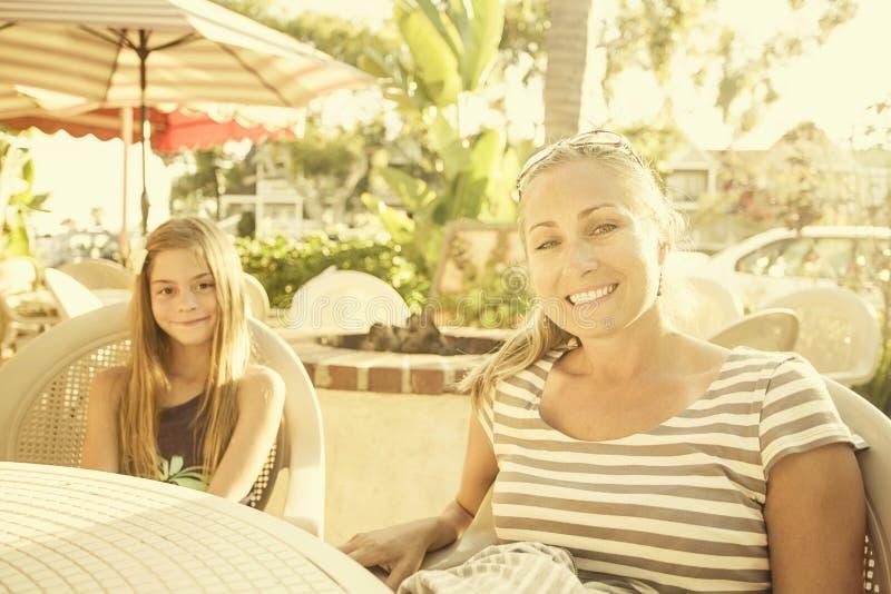 Χαριτωμένο κορίτσι και η μητέρα της που τρώνε σε έναν υπαίθριο καφέ στοκ εικόνα