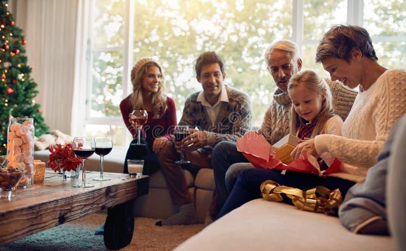 Χαριτωμένο κορίτσι με την οικογένεια και το ανοίγοντας χριστουγεννιάτικο δώρο στοκ εικόνα