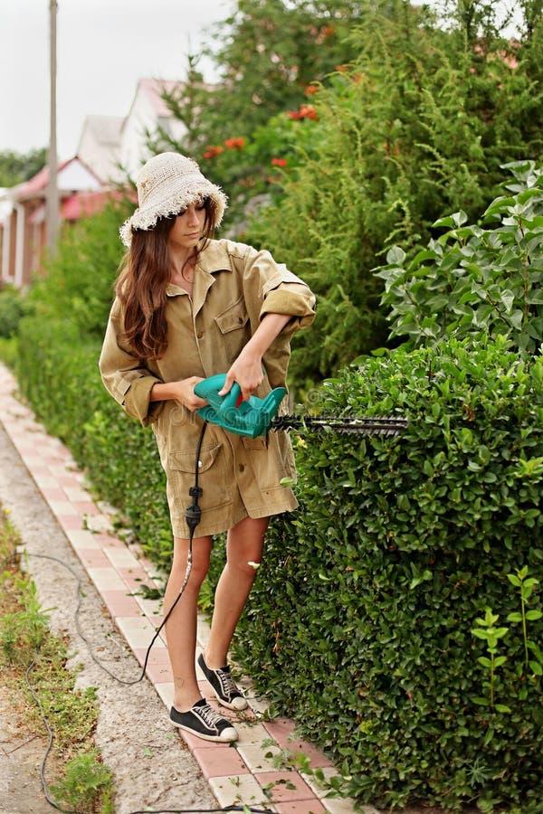 Χαριτωμένο κορίτσι με το μακρυμάλλες τέμνον πυξάρι με ηλεκτρικό trimmer φρακτών στοκ εικόνα