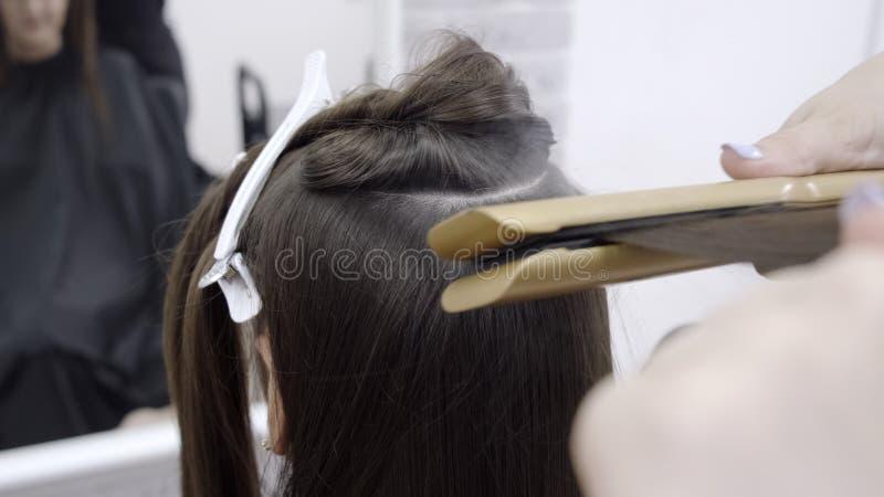 Χαριτωμένο κορίτσι με το μακρύ κομμωτή τρίχας brunette που κάνει την ελασματοποίηση τρίχας σε ένα σαλόνι ομορφιάς έννοια της επεξ στοκ εικόνες