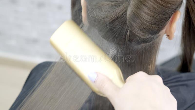 Χαριτωμένο κορίτσι με το μακρύ κομμωτή τρίχας brunette που κάνει την ελασματοποίηση τρίχας σε ένα σαλόνι ομορφιάς έννοια της επεξ στοκ εικόνες με δικαίωμα ελεύθερης χρήσης
