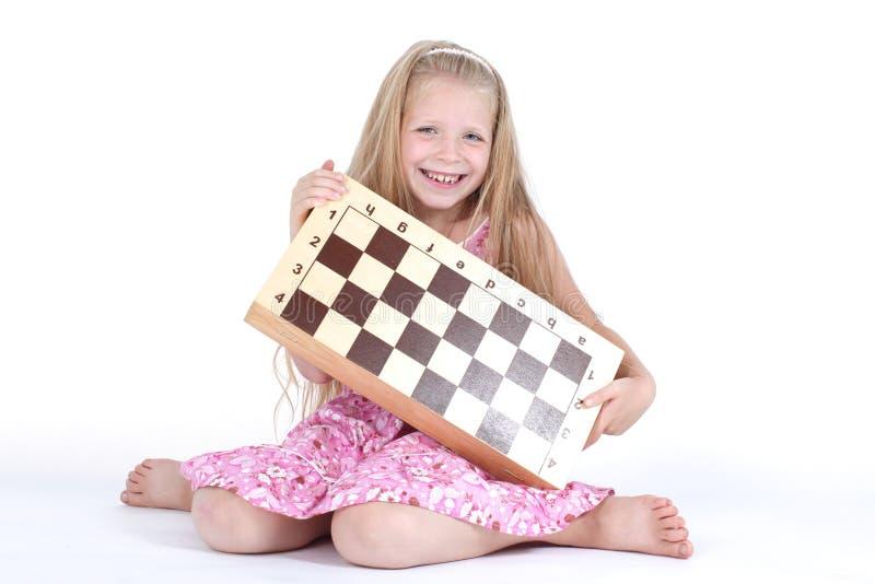 Χαριτωμένο κορίτσι με το σκάκι στο λευκό στοκ εικόνες