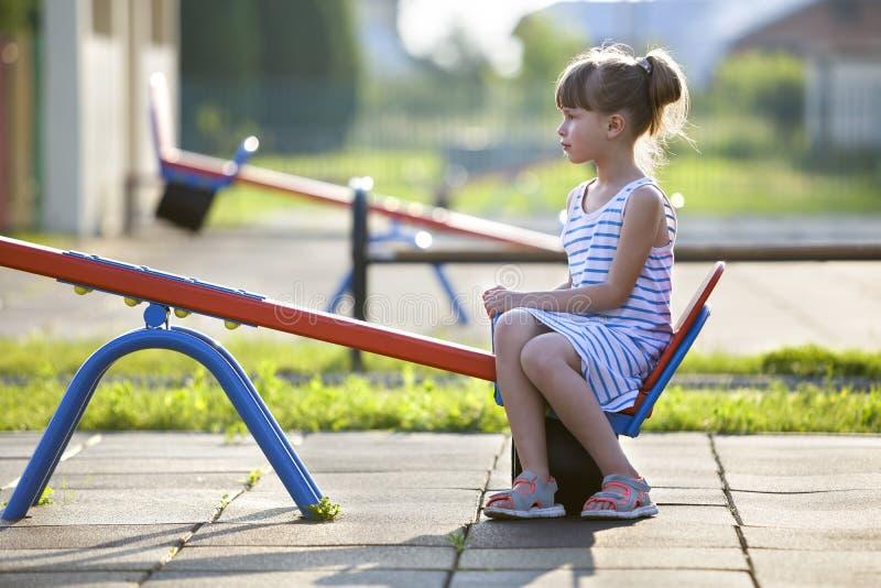 Χαριτωμένο κορίτσι μικρών παιδιών υπαίθρια see-saw στην ταλάντευση την ηλιόλουστη θερινή ημέρα στοκ εικόνες