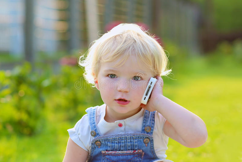 Χαριτωμένο κορίτσι μικρών παιδιών που μιλά με το κινητό τηλέφωνο υπαίθρια στοκ εικόνα με δικαίωμα ελεύθερης χρήσης
