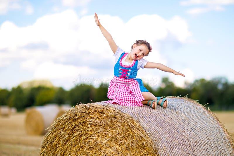 Χαριτωμένο κορίτσι παιδάκι στο παραδοσιακό βαυαρικό κοστούμι στον τομέα σίτου Γερμανικό παιδί με το δέμα σανού κατά τη διάρκεια O στοκ εικόνα