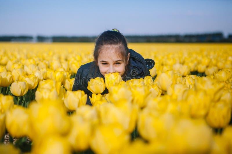 Χαριτωμένο κορίτσι παιδιών που μυρίζει ένα κίτρινο λουλούδι τουλιπών στους τομείς τουλιπών στοκ εικόνες με δικαίωμα ελεύθερης χρήσης