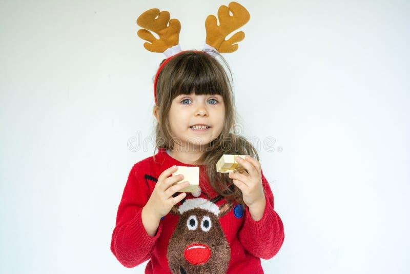 Χαριτωμένο κορίτσι παιδιών που φορά το καπέλο Santa και που επιθυμεί καλές διακοπές στοκ εικόνες