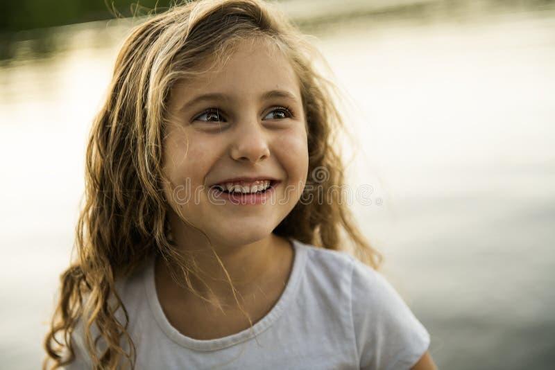 Χαριτωμένο κορίτσι παιδιών σε μια ξύλινη πλατφόρμα από τη λίμνη στοκ εικόνες με δικαίωμα ελεύθερης χρήσης