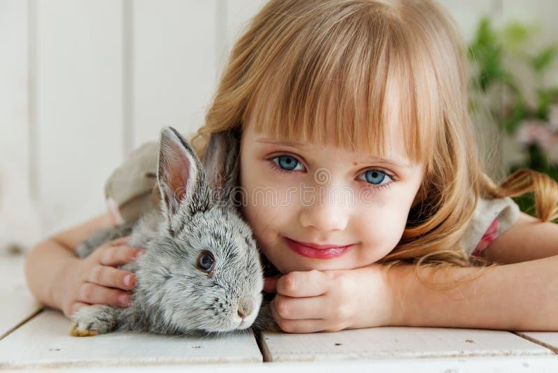Χαριτωμένο κορίτσι που αγκαλιάζει με το κουνέλι στο πάτωμα στο σπίτι στοκ εικόνα