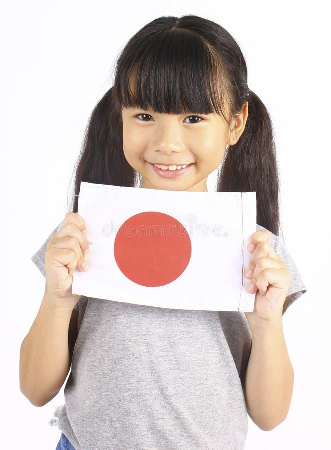 Χαριτωμένο κορίτσι που κρατά την ιαπωνική σημαία στοκ φωτογραφία