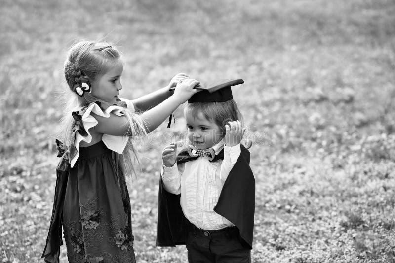 Χαριτωμένο κορίτσι που ντύνει το μικρό αγόρι στο καπέλο και την τήβεννο βαθμολόγησης στοκ φωτογραφία με δικαίωμα ελεύθερης χρήσης