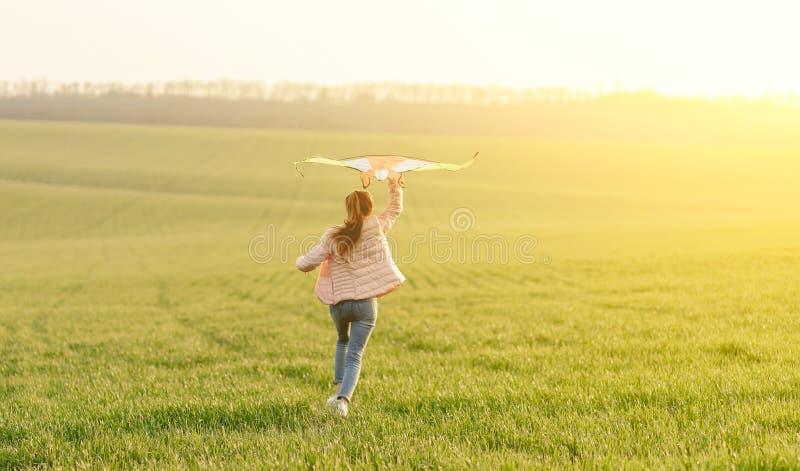 Χαριτωμένο κορίτσι που πετάει φωτεινό χαρταετό στοκ εικόνα με δικαίωμα ελεύθερης χρήσης