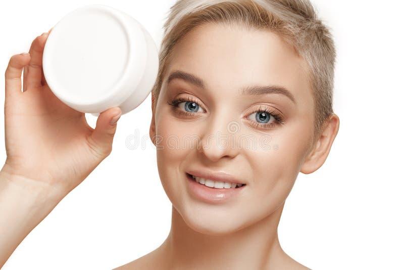 Χαριτωμένο κορίτσι που προετοιμάζεται να αρχίσει την ημέρα της Εφαρμόζει moisturizer την κρέμα στο πρόσωπο στοκ φωτογραφία