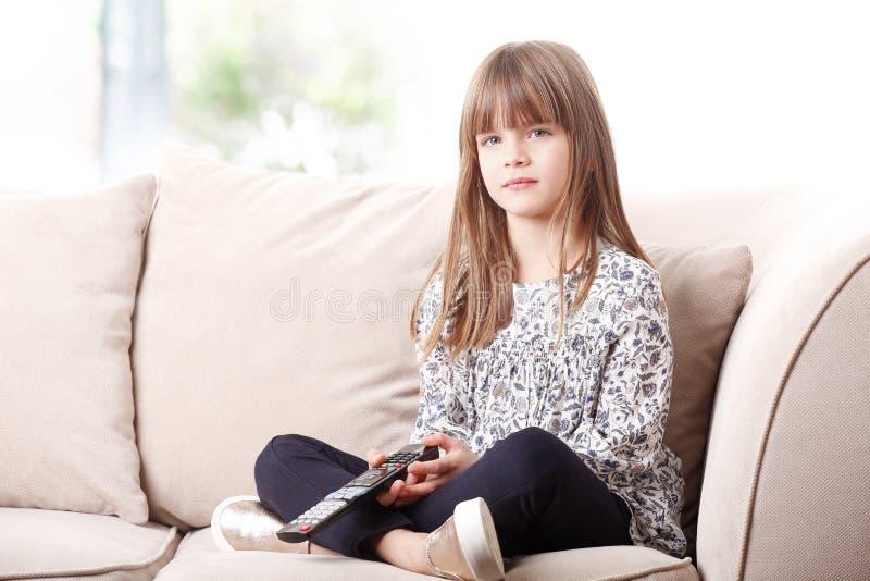 Χαριτωμένο κορίτσι που προσέχει τη TV στο σπίτι στοκ εικόνα