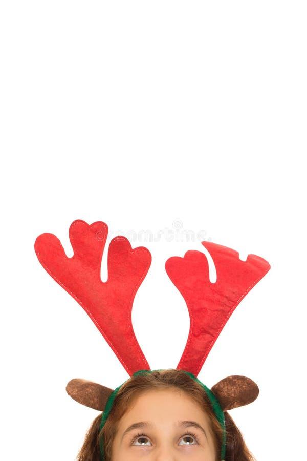 Χαριτωμένο κορίτσι που φορά τα ελαφόκερες Χριστουγέννων στοκ φωτογραφία