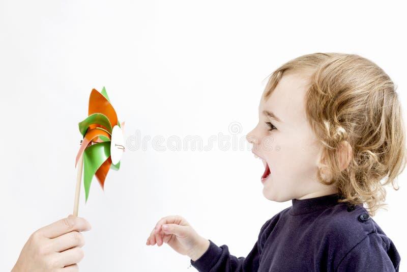 Χαριτωμένο κορίτσι που φυσά στον ανεμόμυλο στοκ φωτογραφία