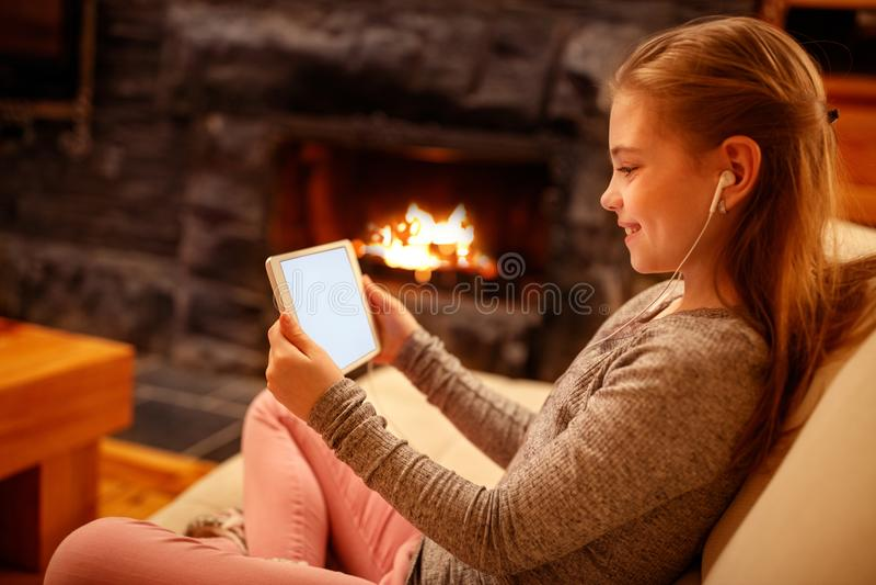 Χαριτωμένο κορίτσι που χρησιμοποιεί iPad την ταμπλέτα ψηφιακών υπολογιστών στο κρεβάτι για το educatio στοκ φωτογραφίες