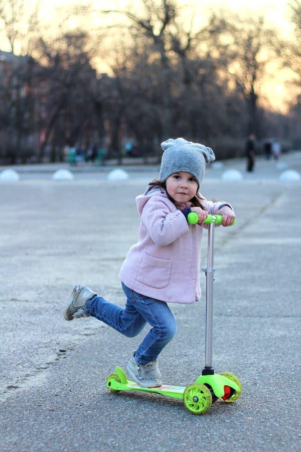 Χαριτωμένο κορίτσι σε ένα καπέλο, ένα παλτό και τα τζιν που οδηγούν ένα τρίτροχο μηχανικό δίκυκλο Ηλιοβασίλεμα πόλεων άνοιξη βραδ στοκ εικόνα