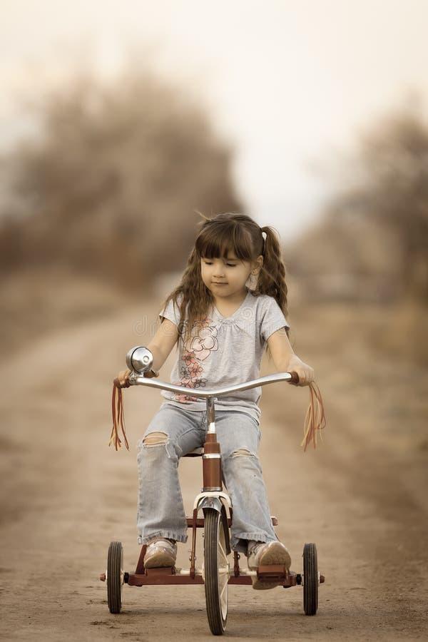 Χαριτωμένο κορίτσι σε τρίκυκλο όλοι για τα εξαρτήματα στοκ εικόνα