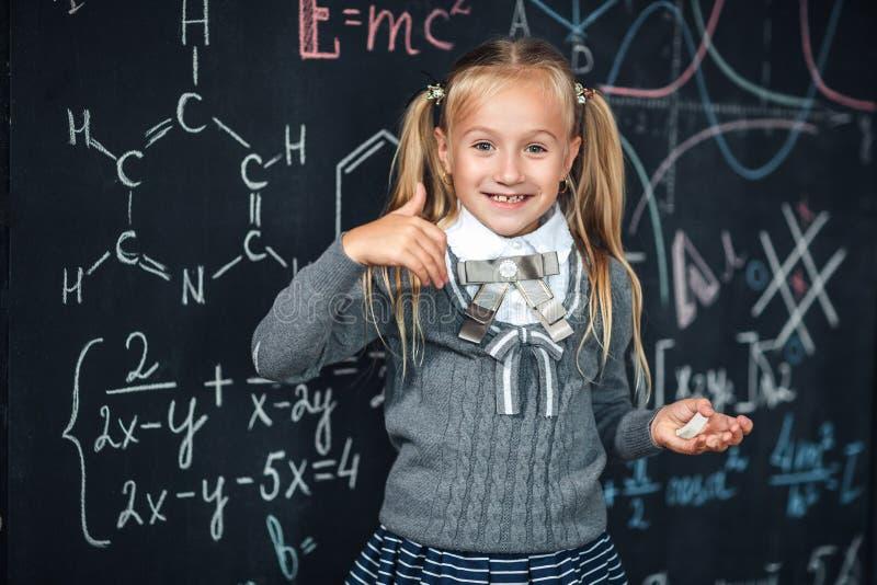 Χαριτωμένο κορίτσι στη σχολική στολή Πηγαίνετε στο σχολείο για πρώτη φορά Το κορίτσι στο εσωτερικό του δωματίου κατηγορίας με τον στοκ φωτογραφίες