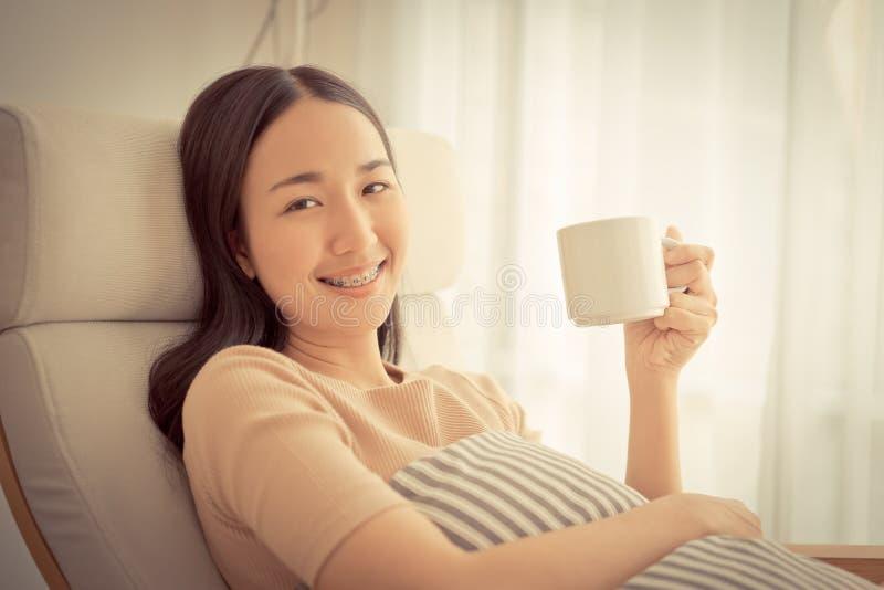 Χαριτωμένο κορίτσι στον καφέ συνεδρίασης και κατανάλωσης καναπέδων από το windo στοκ φωτογραφίες