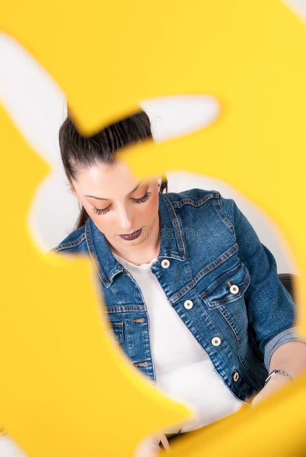 Χαριτωμένο κορίτσι στο κίτρινο πλαίσιο κουνελιών στοκ εικόνα με δικαίωμα ελεύθερης χρήσης