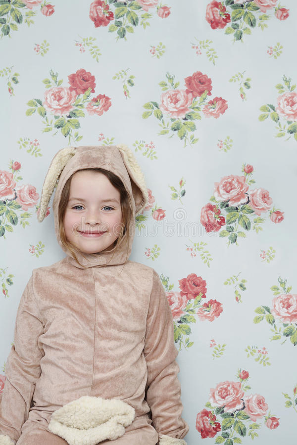 Χαριτωμένο κορίτσι στο κοστούμι λαγουδάκι ενάντια στην ταπετσαρία στοκ εικόνες