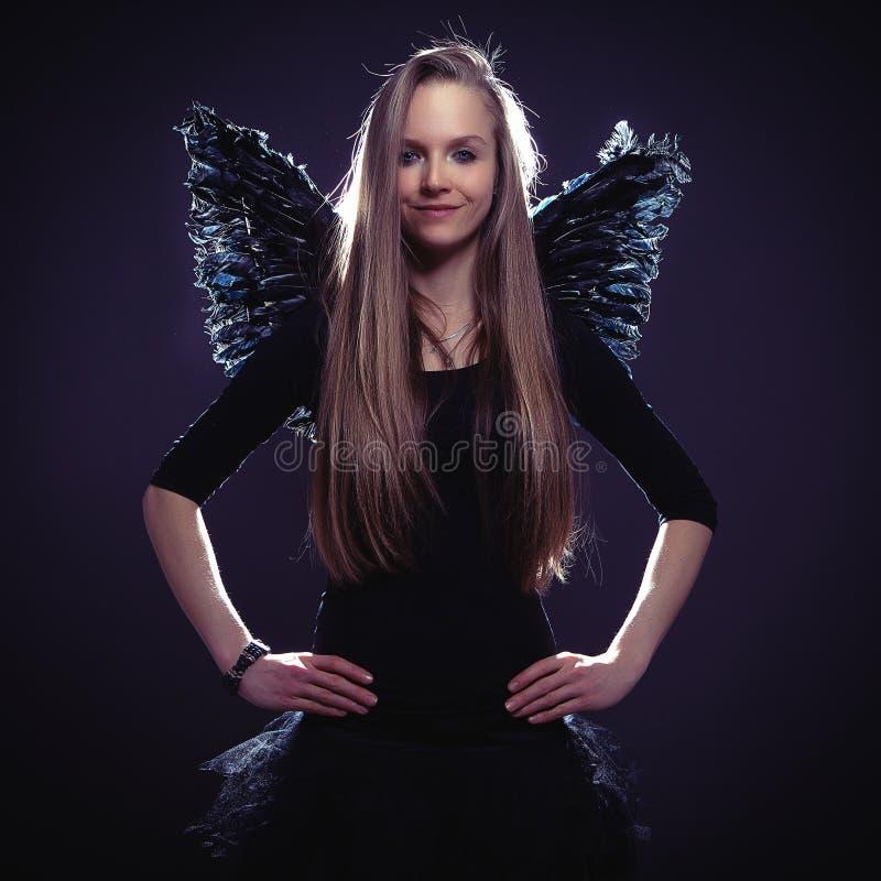 Χαριτωμένο κορίτσι στο σκοτεινό κοστούμι αγγέλου στοκ φωτογραφίες