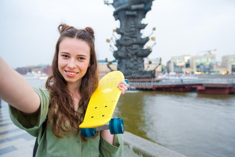 Χαριτωμένο κορίτσι hipster makihg selfie με skateboard υπαίθρια στο φως ηλιοβασιλέματος Ενεργός φίλαθλη γυναίκα που έχει τη διασκ στοκ φωτογραφίες με δικαίωμα ελεύθερης χρήσης