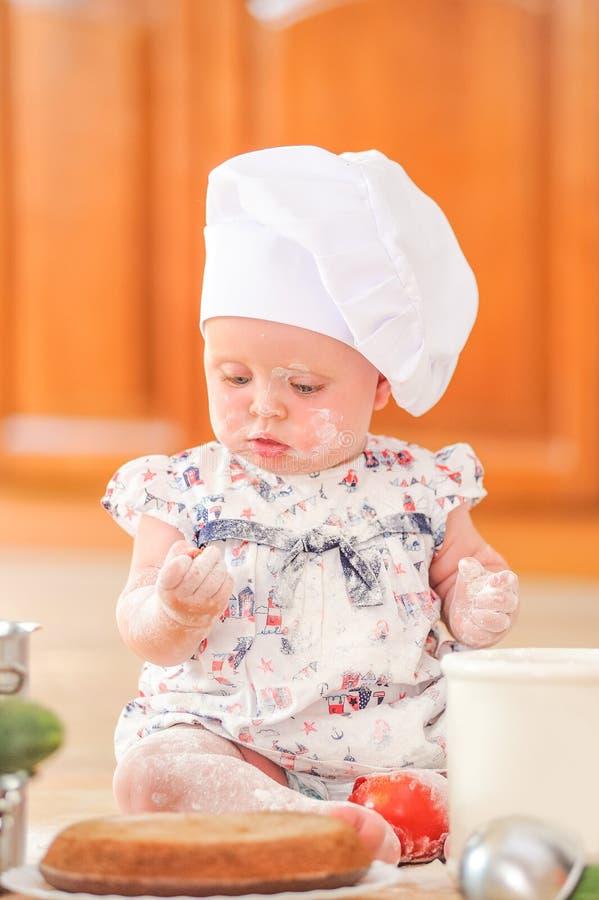 Χαριτωμένο κορίτσι liitle στη συνεδρίαση καπέλων αρχιμαγείρων ` s στο χώμα πατωμάτων κουζινών στοκ φωτογραφία