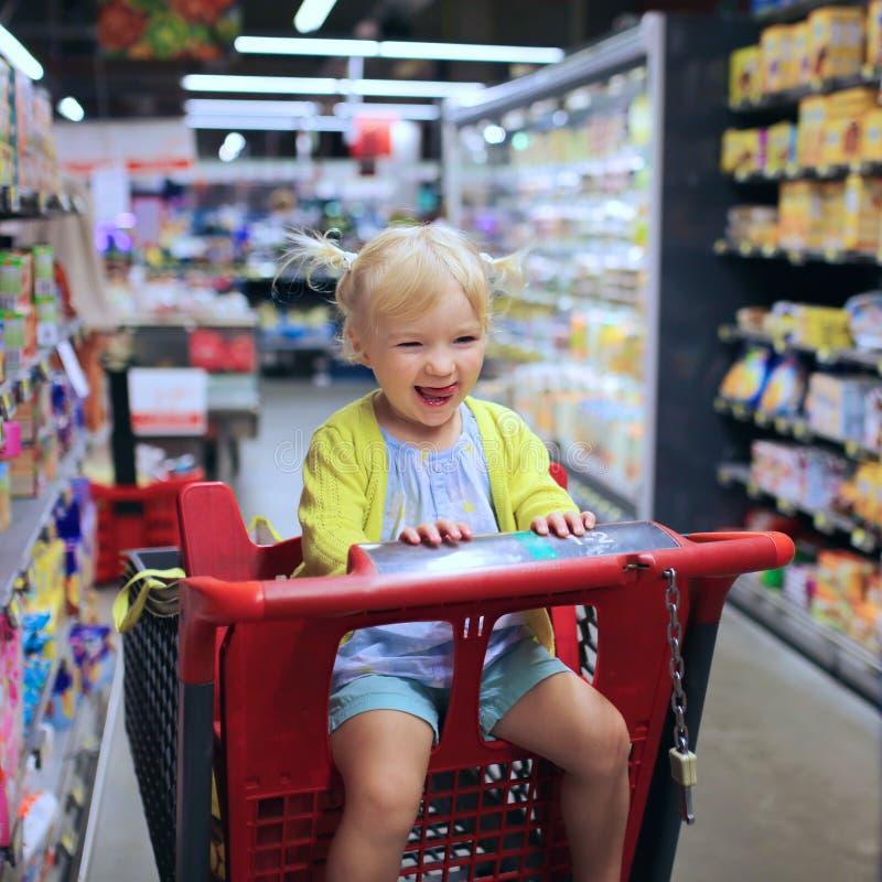 Χαριτωμένο κορίτσι preschooler στο κάρρο αγορών στοκ εικόνες