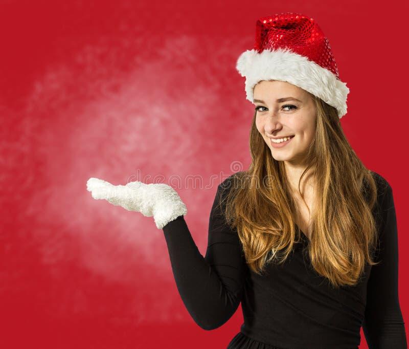 Χαριτωμένο κορίτσι santa που παρουσιάζει κάτι σε ετοιμότητα ανοικτό στο κόκκινο backgro στοκ εικόνες με δικαίωμα ελεύθερης χρήσης