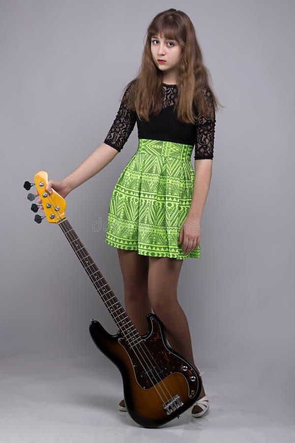 Χαριτωμένο κορίτσι tenage στο φόρεμα με την κιθάρα στοκ φωτογραφία με δικαίωμα ελεύθερης χρήσης