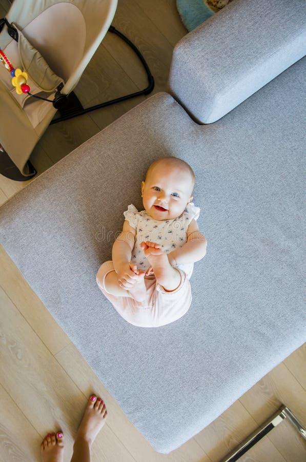 Χαριτωμένο κοριτσάκι με τα μπλε μάτια που παίζουν στον καναπέ στοκ φωτογραφίες με δικαίωμα ελεύθερης χρήσης